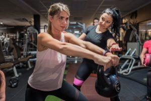 Muskeln aufbauen, Fotoshooting für Betreuung im Fitnessstudio Studio21 in Nürnberg mit Fitness Model Oxana und einer sportlichen Kundin mit einer Kettle Bell
