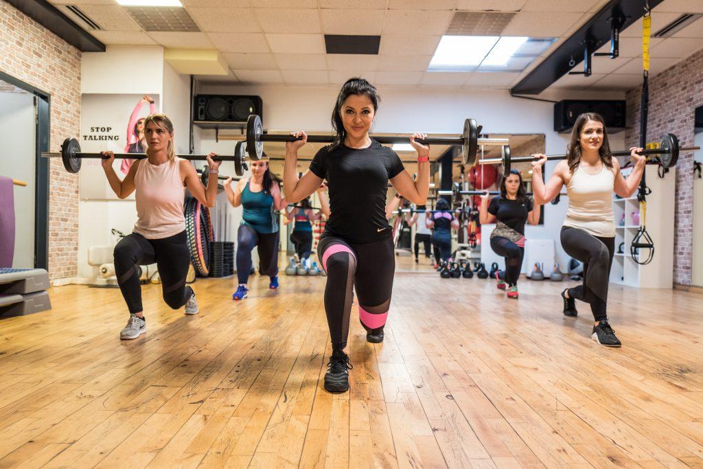 starke Kurse im Fitnessstudio Studio21 in Nürnberg mit Fitness Model Oxana und einigen fitten Mädels im Hintergrund mit Langhantel
