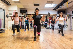 Sport, starke Kurse im Fitnessstudio Studio21 in Nürnberg mit Fitness Model Oxana und einigen fitten Mädels im Hintergrund mit Langhantel